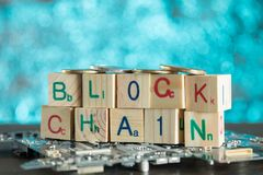 Blockchain cryptocurrency concept. Wood blocks say block chain w. Ith binary code on motherboard with crypto currency coins on green background royalty free stock image