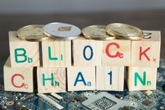 Blockchain cryptocurrency concept. Wood blocks say block chain w. Ith binary code on motherboard with crypto currency coins stock photography