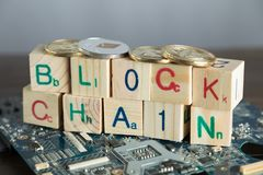 Blockchain cryptocurrency concept. Wood blocks say block chain w. Ith binary code on motherboard with crypto currency coins royalty free stock images