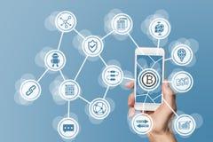 Blockchain i bitcoin pojęcie unaoczniający telefonem komórkowym i błękitnym tłem fotografia stock