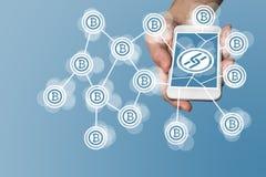 Blockchain och bitcoinbegreppet med den moderna handen som rymmer, ilar telefonen som exemplet för fenatechteknologi Fotografering för Bildbyråer