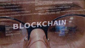 Blockchain text on background of developer. Blockchain text on the background of female software developer. Eyes of woman with glasses are looking at programming stock footage