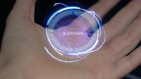 Blockchain text hologram on a female hand. Blockchain text in a round conceptual hologram on a female hand. Close-up of a hand on a black background with future stock footage