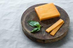 Blockcheddar-käse, Scheiben und Basilikumblätter Stockfotografie