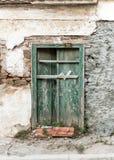 Blocked old green wooden door with cracks, on weathered wall. Blocked old green wooden door with cracks, on weathered wall royalty free stock photo