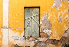 Blocked old wooden window, on yellow painted weathered wall. stock photos