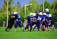 Blocken des Jugend-amerikanischen Fußballs Stockfotografie