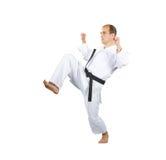 Blockhände und Trittbein tut einen Athleten im karategi stockfotografie
