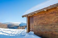 Blockhaus bedeckt mit Schnee Stockfotografie