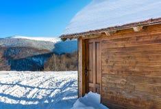 Blockhaus bedeckt mit Schnee Stockbilder