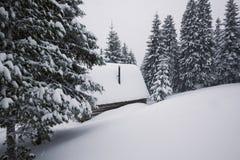 Blockhaus in den Winterbergen wird mit Schnee bedeckt Stockfotografie