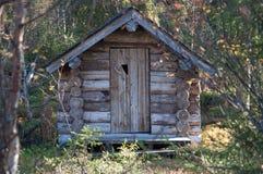 Blockhaus herein in tiefem Taiga-Wald Stockfotografie