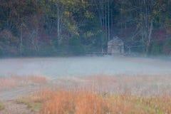 Blockhaus im Morgen-Nebel Lizenzfreies Stockbild