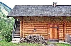 Blockhaus mit kleinem Fenster-, Tür- und Holzstapel Stockbild
