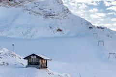 Blockhaus- und Skiaufzug auf einem schneebedeckten Berghang Stockfotografie