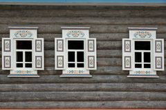 Blockhaus-Wand mit drei Ornamental Windows Stockbild