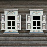 Blockhaus-Wand mit zwei Ornamental Windows Stockbild