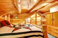 Blockhausschlafzimmer unter hölzerner großer Decke. Stockfoto