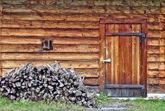 Blockhauswand mit kleinem Fenster-, Tür- und Holzstapel Stockbilder