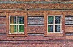 Blockhauswand mit zwei Fenstern Lizenzfreie Stockfotografie