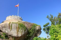 Blockhouse and chinese flag on the rock, srgb image. Abandoned bunker by huandaolu road, xiamen city, china. ancient military facilities become tourism resources Royalty Free Stock Photography