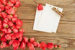 Blockieren Sie Anmerkungen und rote Rosen auf hölzernem Hintergrund Lizenzfreie Stockfotografie