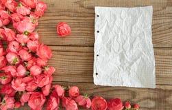 Blockieren Sie Anmerkungen und rote Rosen auf hölzernem Hintergrund Lizenzfreie Stockbilder