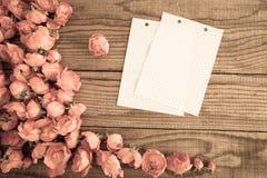 blockieren Sie Anmerkungen und rote Rosen auf hölzernem Hintergrund, das E-F Weinlesedenim Lizenzfreies Stockbild