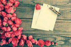 blockieren Sie Anmerkungen und rote Rosen auf hölzernem Hintergrund, das E-F Weinlesedenim Lizenzfreie Stockbilder