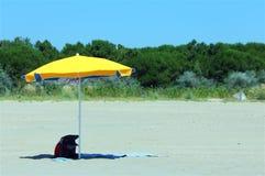 blockieren Sie gelben Regenschirm auf dem sonnigen Strand im Sommer Lizenzfreies Stockfoto