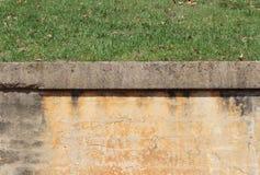 Blockieren Sie Stützmauer mit Gipsende, konkreter Kappe und Gras Stockfotografie