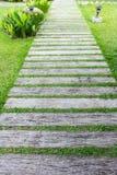 Blockieren Sie Wegweg im Garten mit grünem Gras Stockfoto