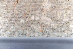 Blockieren Sie Zementwand mit Straße im schmutzigen Asphalt des Vordergrunds voran Stockfotografie