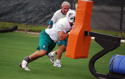 Blocking Sled Workout. Miami Dolphin lineman hitting a blocking sled under the watchful eye of one of the line coaches Stock Image