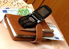 Blocknote, téléphone portable et billets de banque Images stock