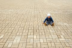 Blocks. Cold summer. The boy sits on a stone blocks Stock Images