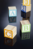 Blocks. Childrens toy blocks spelling out ABC on a reflective surface royalty free stock images