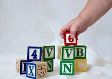 Blocks and baby hand. A baby's hand picking up a block from a stack stock images