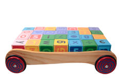 Blocks in back of wooden trolley isolated on whit. Childrens toy letter building blocks all together in a toy cart isolated on white background Royalty Free Stock Photo