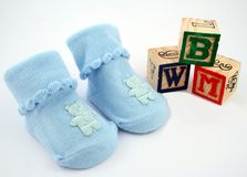 Blocks and Booties. A pair of blue baby booties beside some wooden blocks Royalty Free Stock Photography