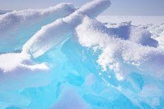 Blocks of broken blue ice on sky background. Winter Baikal lake stock images