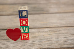 Blocks displaying love message and Red heart shape Stock Photo