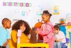 Blocks game in kindergarten kids and teacher stock image