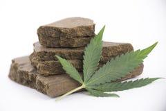 Blocks of hashish, a medical marijuana concentrate  with. Blocks of hashish, a medical marijuana concentrate  on white with cannabis leaf Stock Image
