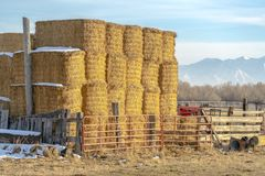 Blocks of hay piled inside a fenced area on a farm in Eagle Mountain Utah. A scenic background of mountain and sky can be seen on this sunny winter day royalty free stock photography