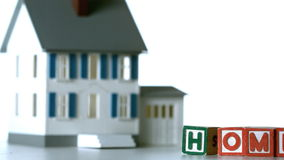Blocks in row spelling home sliding along in front of a model house Stock Images