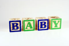 Blocks that spell baby. Childrens blocks lined up to spell BABY royalty free stock photography