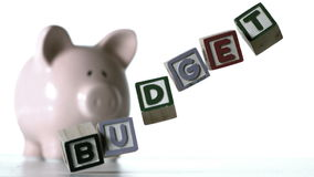 Blocks spelling budget falling over in front of a piggy bank Royalty Free Stock Photo