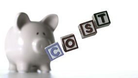 Blocks spelling cost dropping down beside a piggy bank Stock Photos