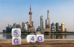 Blocks spelling 5G on wooden table with cityscape of Shanghai behind stock photos